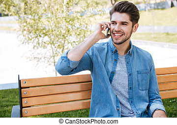 Portrait of a young man sitting on the bench talking