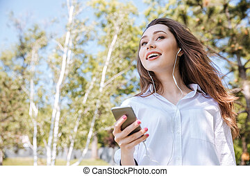 Young happy woman listening music at the park - Young happy...