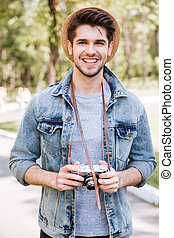Close-up portrait of a handsome guy holding camera outdoors