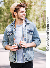 Portrait of a handsome guy holding camera outdoors -...