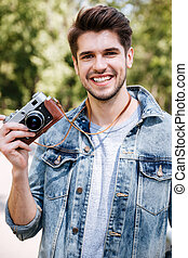 Close-up portrait of a handsome guy holding camera outdoors...