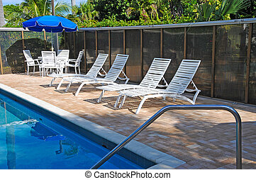 Pool Side Area - Chaise Lounges and Table by Swimming Pool