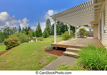 Wooden front deck of home with green lawn