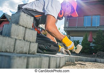 Building Brick Garden Path. Caucasian Worker Building Block...
