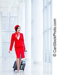 Stewardess - Young stewardess with a suitcase at airport