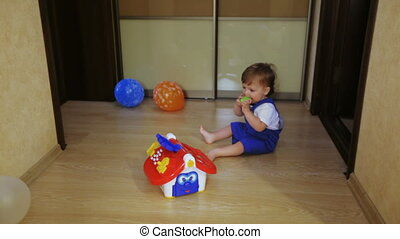 Child on floor playing with toy house - On hardwood floor...