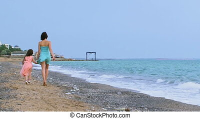 Two walking along the shore - An adult woman and a young...