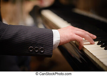 Close-up of a music performers hand playing the piano
