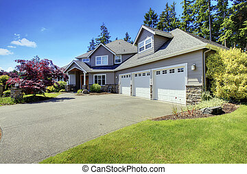 Luxury house exterior with french windows and three space parking garage.