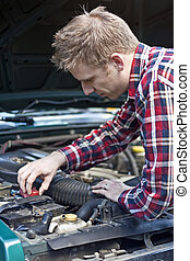 Young Blond Mechanic - Young blond male mechanic working on...