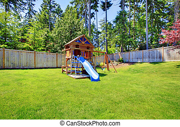 Play kids ground area with chute in fenced backyard.