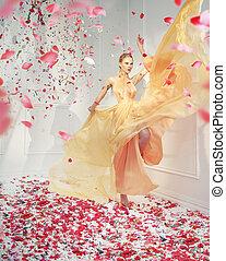 Fabulous young woman in the petal's rain