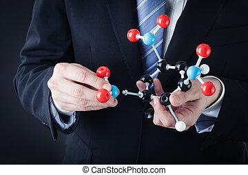 assembling a tnt molecular structure - a businessman wearing...