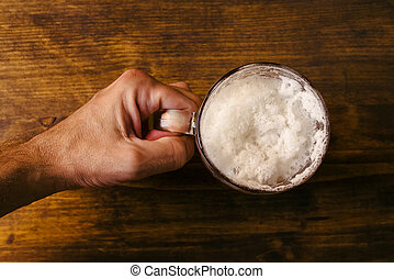 Hand holding beer mug full of cold fresh alcohol drink on...