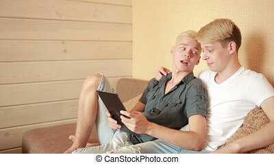 Happy gay couple using tablet in bed gay couple - Happy gay...
