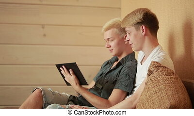 Happy gay couple using tablet in bed.