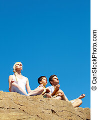 Balance - Photo of three family members sitting on cliff in...