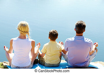 Meditation - Rear view of three family members in pose of...