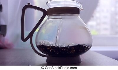 brewing black tea with hot water in the teapot - brewing...