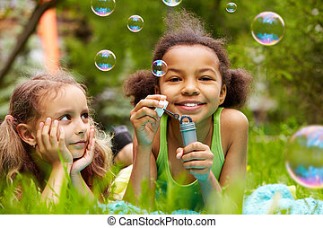 Bubble fun - Portrait of cute girl blowing soap bubbles with...