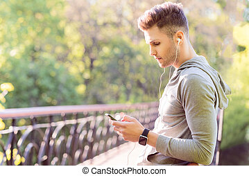 Thoutful male runner using modern technology - Pensive young...