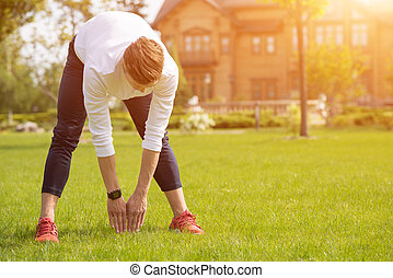 Fit male athlete doing exercise on grass - Healthy young man...