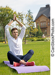 Relaxed male athlete meditating on grass - Attractive young...