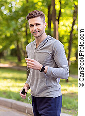 Happy young man running with earphones - Joyful male...