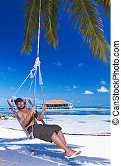 Man at Maldives - Handsome man resting near water at...