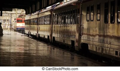 Wet rail station platform with train carriages standing and...