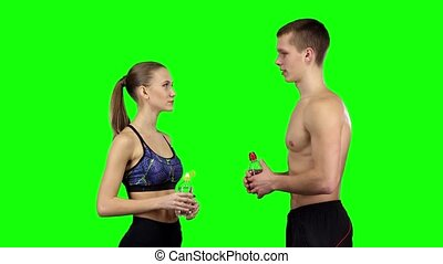 Couple with water bottles. Green screen - Man and woman...