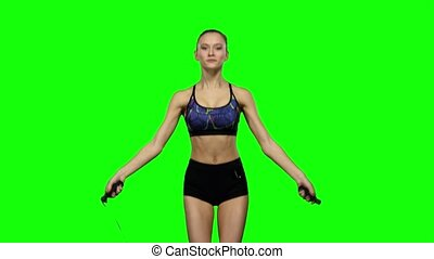 Woman is jumping with a skipping rope. Green screen - Slim...