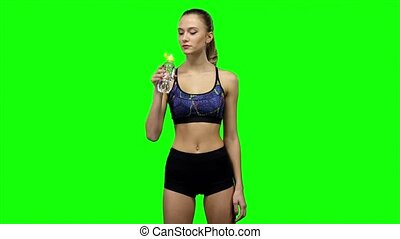 Woman in sportswear drinking water from bottle. Green screen...