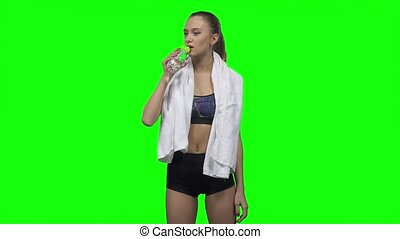 Sportswoman is drinking water and towels. Green screen -...