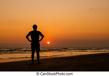Man silhouette stand alone on the beach and watching...