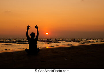 Man silhouette doing yoga exercise at sunset beach