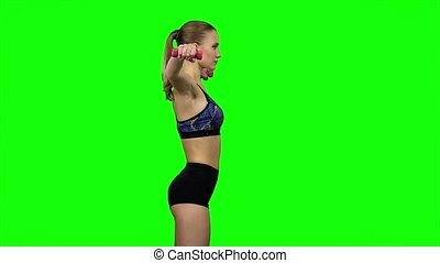 Girl with dumbbells in profile Green screen - Young woman...