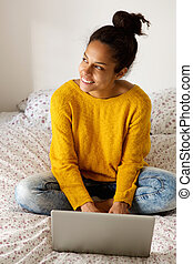Young woman sitting on bed with laptop