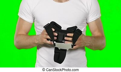 Male hand taking a virtual reality headset Green screen Slow...