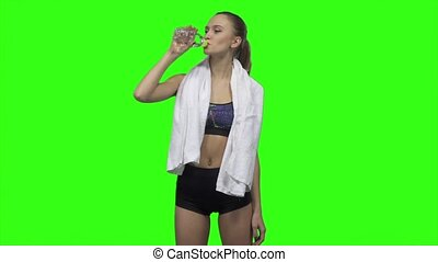 Woman is drinking water and towels. Slow motion. Green...