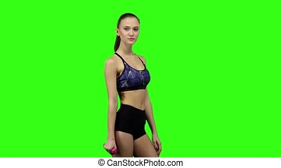 Girl is engaged with weights in one hand. Slow motion. Green screen