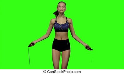 Girl is jumping with a skipping rope. Slow motion. Green...