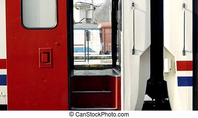 Open train door with another train moving in background