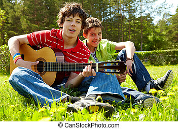 Summer song - Portrait of happy lad playing the guitar with...