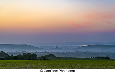 Corfe Castle sunset with mist rolling in - Rainbow skies in...