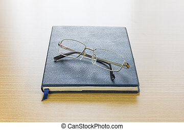 Glasses put on a book on wood table background