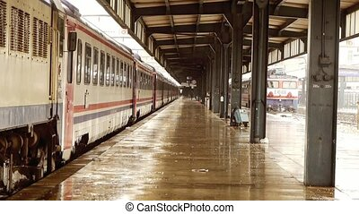 Wet rail station platform with train carriages standing in...