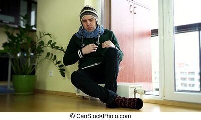 man strip warm cap and scarf sitting on heater near balcony...