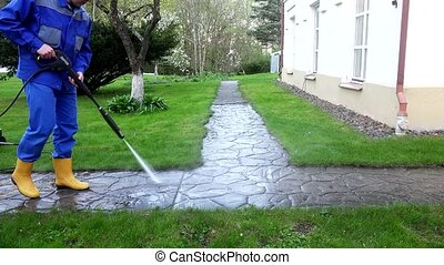 Professional worker spray concrete path with special high pressure tool.