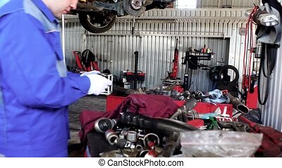 Engineer man expecting used car part in garage.
